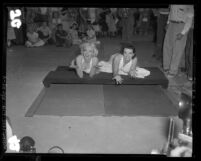 Marilyn Monroe and Jane Russell putting handprints in cement at Chinese Theater, Hollywood (Los Angeles), 1953