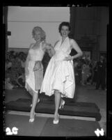 Marilyn Monroe and Jane Russell putting footprints in cement at Chinese Theater, Hollywood (Los Angeles), 1953