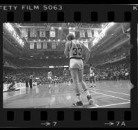 Courtside view looking up at banners, as Celtics' Larry Bird watches players at opposite end of court during NBA championship game in Boston, Mass., 1984