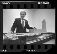 Rapid Transit District manager, John Dyer posing with model of Wilshire and Western Metro Red Line subway station in Los Angeles, Calif., 1984