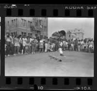 Primo Desidero performing freestyle skateboarding as crowd looks on in Venice Beach, Calif., 1984