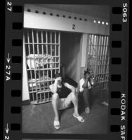 Two males sitting on floor in front of cells in Los Angeles County Juvenile Hall, 1984