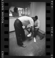 Officer removing manacles from a boy in Los Angeles County Juvenile Hall, 1984