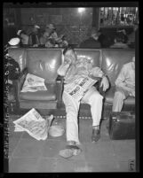 """Sgt. B.A. Kainer napping at Union Station with August 12, 1945 with newspaper in his lap, headline reads """"WORLD WAITS"""""""