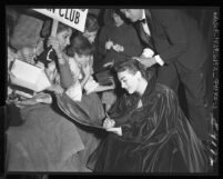 "Actress Joan Crawford signing autographs for fans at premiere of her film, ""Torch Song"""