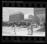 Shoppers at Century City Shopping Center which is decorated with 1984 Olympics banners, Los Angeles, 1984