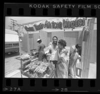Samuel Bassey serving barbecued chicken to Joan Murray at booth in Leimert Park in Los Angeles, Calif., 1984