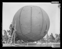 Norman Tremblay, Sanitation District engineer, examining sewage gas storage sphere in Orange County, Calif., 1964