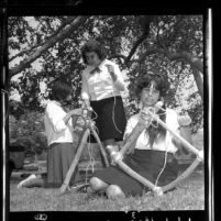 Three Crescenta Valley Camp Fire Girls constructing chairs out of tree limbs in Glendale, Calif., 1964