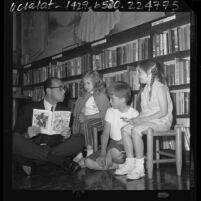Children's books author, Sid Fleischman sitting on floor of library reading to three children in Santa Monica, Calif., 1964