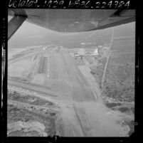 Aerial view of single engine plane above runway and surrounding terrain at Cable Airport in Upland, Calif., 1964