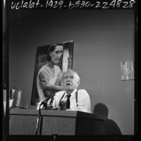 """Upton Sinclair talking to reporters about photographic exhibit, """"The Bitter Years: 1935-1941,"""" Los Angeles, 1964"""