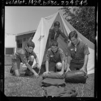 Four Boy Scouts rolling up sleeping bags before leaving to National Jamboree at Valley Forge, Penn., 1964