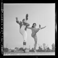 Los Angeles Ram's kicker Danny Villanueva in uniform doing the can-can with actress Susan Hart, 1964