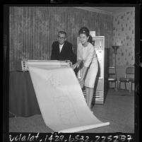 """L. Pyle and Nonna Walls examine a print out of """"Miss Formula"""", a computer created rendering of the """"perfect female,"""" Calif., 1964"""