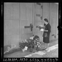 Woman placing flowers at tomb of Marilyn Monroe on second anniversary of Monroe's death, Westwood, Calif., 1964