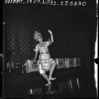 Thai American dancer wearing silver beaded costume practicing for festival in honor of Thai queen's birthday, Los Angeles, Calif., 1964