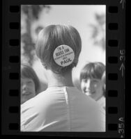 """Girl with button pinned in her hair reading """"I'm A Beatle Fan In Case of an Emergency Call Paul"""" in Los Angeles, Calif., 1964"""
