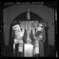 Rabbi Isaiah Zeldin with student Rabbi Harvey Block holding Torah scrolls in front of new Ark at Stephen S. Wise Temple, Los Angeles, Calif., 1964