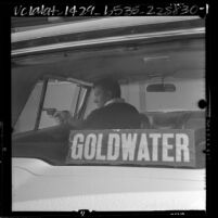 Policeman DeWayne Anderson reenacting altercation with two men who demanded he remove Goldwater sticker from car, Calif., 1964