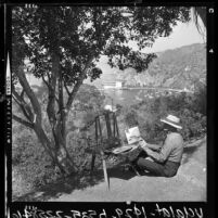 Frank W. McElroy painting on trail along cliff overlooking Avalon, Catalina Island, Calif., 1964