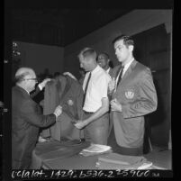 U.S. Olympic athletes Jerry Shipp and Bill Bradley receiving team jackets by official George J. Gulack, 1964