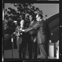 Steve Santangelo, of California Junior Chamber of Commerce, handing 1964 Olympic torch to Los Angeles Mayor Samuel W. Yorty
