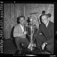 Race car driver Parnelli Jones and Payton Cramer with Los Angeles Times Grand Prix trophy, 1964