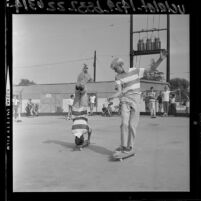 George Trafton doing headstand on skateboard as Danny Bearer watches at skateboarding event in Covina, Calif., 1964