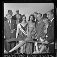 Edmund G. (Pat) Brown, surrounded by Robert E. McClure, beauty contestants and others, cutting ribbon at dedication of section of Santa Monica Freeway, 1964