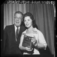 Shirley Temple Black posing with award she received from the California Teachers Association, 1964
