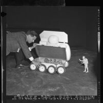 William Sponsler, designer working with one-sixth scale model of a Lunar Surface Vehicle, 1964