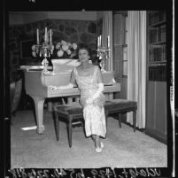 Composer Elinor Remick Warren in evening dress, seated at piano, 1964