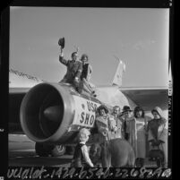 Bob Hope perched on jet engine as other entertainers gather before leaving on Christmas USO tour, 1964