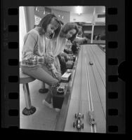 Boys and girls racing slot cars at racing center in Panorama City, Calif., 1964