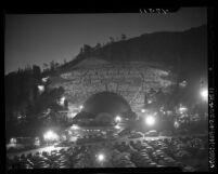 View from across parking lot of stage and crowd on hillside during performance of Margaret Truman at the Hollywood Bowl, Calif., 1947