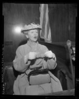 Gossip columnist Hedda Hopper, posing for camera on witness stand during forgery trial in Los Angeles, Calif., 1955