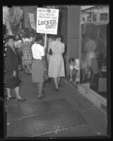 "Lady garment workers picketing as store manager Dave Schultz draws ""don't cross"" line on sidewalk in Los Angeles, Calif., 1947"