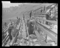 Workmen cleaning up the rubbish and bottles in the stands after a football game at Los Angeles Coliseum