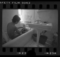 Man washing dishes in bathtub in Frostonya Apartment-Hotel slum in Los Angeles, Calif., 1984