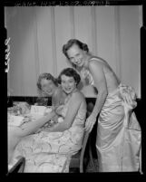 Three Los Angeles, Calif. Junior Leaguers in evening gowns at benefit for Community Trust Fund in 1955