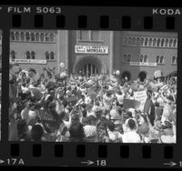 Crowd waving Mondale/Ferraro placards at Walter Mondale during campaign stop at USC, 1984