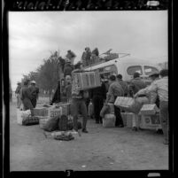 Braceros loading their belongings onto a bus for trip home to Mexico, El Centro, 1965