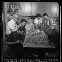 Members of Ontario Rockhound Club clustered around table making jewelry, Calif., 1965