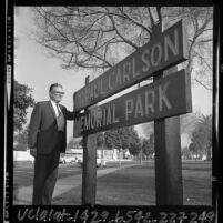"Mayor William Botts standing besides signpost of  ""Dr. Paul Carlson Memorial Park"" in Culver City, 1965"