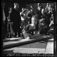Actress Debbie Reynolds smiling and displaying cement-covered hands after making imprint at Grauman's Chinese Theater, Hollywood (Los Angeles), 1965