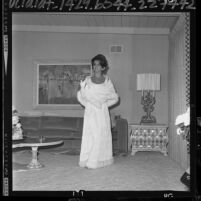 Actress Ann-Margret in livingroom, modeling gown she will wear to Lyndon Johnson's Inaugural Ball, 1965