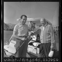 Richard Nixon and Dwight Eisenhower posing next to cart while golfing in Southern California, 1965