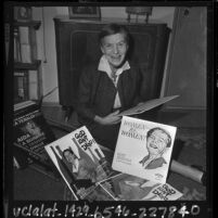 Christian lecturer Gertrude Behanna sitting on floor with collection of her records, Calif., 1965