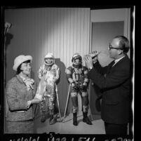 Frank J. Roberts, Apollo engineer demonstrating how astronauts eat to ARCS treasurer, Marion DeFore, Calif., 1965